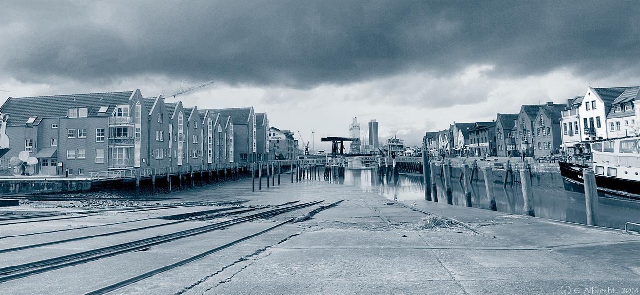 """Tidehafen in Husum (Nordfriesland - linksseitig """"Neues Wohnen"""" rechtsseitig: touristisches Stadtzentrum, in der Ferne Windkraft und äußere Hafenanlagen"""